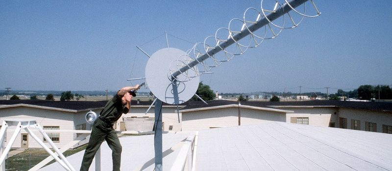 A member of the Air Force Communications Command directs a satellite communications antenna used with the Hammer Ace system.  Hammer Ace is a secured long-range, air-transportable communications system used for rapid response purposes.  From the June 1984 Airman Magazine.